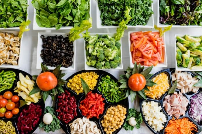 Salad bar with greens, broccoli, black olives, and more