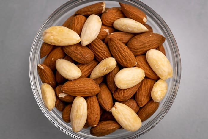 Peeled and unpeeled almonds in a glass bowl